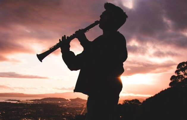 person at dawn backlit plating a clarinet